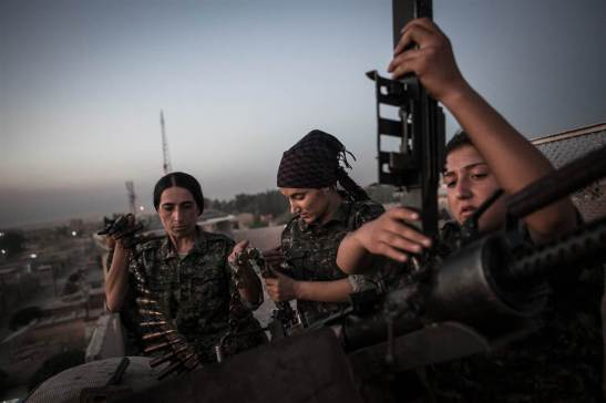 In the dry and desolate land along Syria's northeastern border, thousands of young Kurdish women have taken up arms to protect their people against attacks from Bashar Assad's government, ISIS militants and the al Qaeda-linked al-Nusra Front. Some 7,000 volunteer soldiers have joined the Women's Protection Unit, or YPJ, which grew out of the wider Kurdish resistance movement. The group is strongly associated with the PKK, an organization fighting for the rights of Kurds in neighboring Turkey that has been designated a terrorist group by the U.S. State Department. Alongside Kurdish Peshmerga forces, the YPJ has been battling against Islamic militants who have seized large areas of Iraq and Syria and declared a cross-border caliphate. ABOVE: YPJ Captain Ronahi Anduk, 34, left, Gian Dirik, center, and Dirsim Judi, 18, right, work on a Dushka weapon in the town of Til Kocer, Syria.