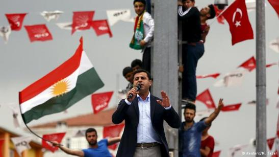 Selahattin Demirtas, co-chairman of the pro-Kurdish Peoples' Democratic Party (HDP), speaks as his supporters wave Kurdish (L) and Turkish national (R) flags in the background. REUTERS/MURAD SEZER