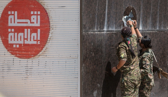"""Kurdish People's Protection Units (YPG) fighters remove an Islamic State sticker in Tel Abyad town, Raqqa governorate, June 16, 2015. With a string of victories over Islamic State, Syria's Kurds are proving themselves an ever more dependable ally in the U.S.-led fight against the jihadists and building influence that will make them a force in Middle Eastern politics. Aided by U.S.-led air strikes, the Kurdish-led YPG militia may have dealt Islamic State its worst defeat to date in Syria by seizing the town of Tel Abyad at the Turkish border, cutting a supply route to the jihadists' de facto capital of Raqqa city. The Arabic text on the left read: """"Media point"""". REUTERS/Rodi Said - RTX1GSTO"""